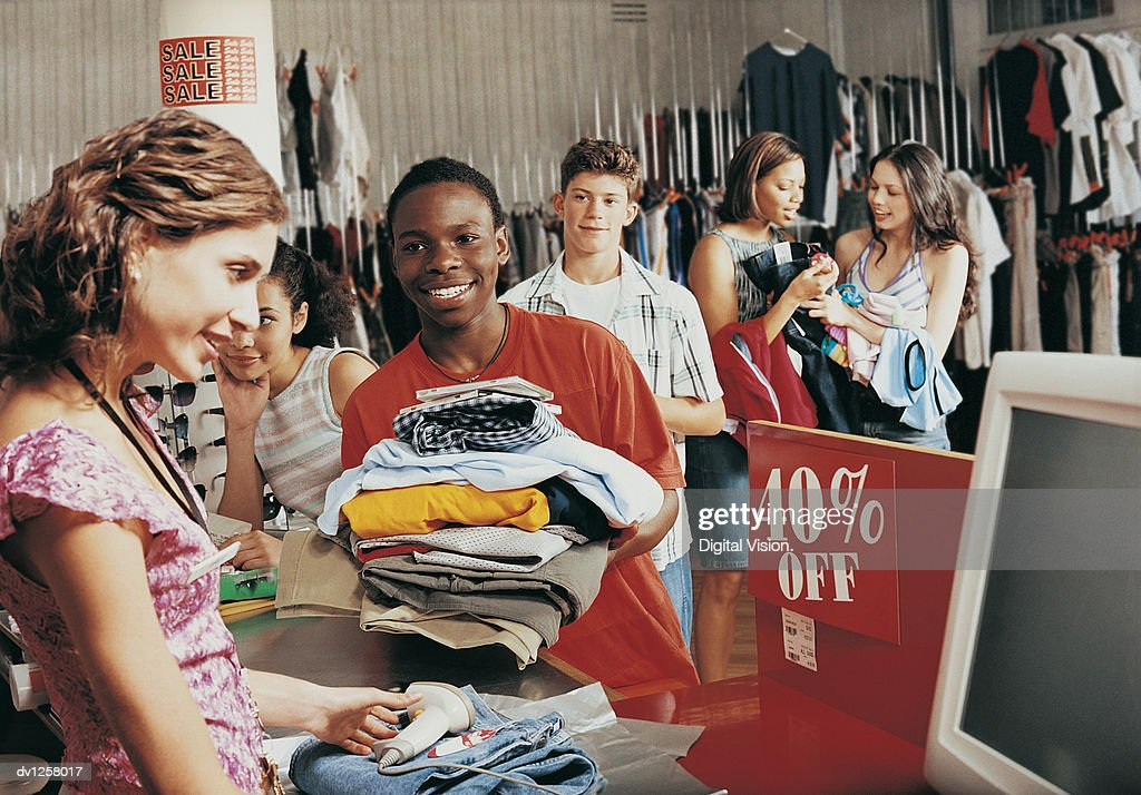 Young Boy Buying a Stack of Clothing From a Shop Assistant at a Checkout Counter in a Clothes Shop