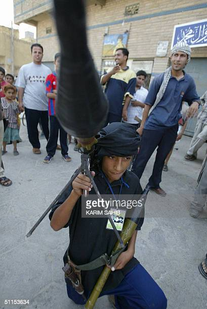A young boy carries a grenade launcher as militiamen loyal to radical Iraqi Shiite Muslim cleric Moqtada Sadr celebrate after an attack on a police...