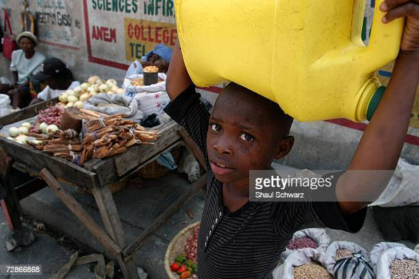A young boy carries a huge water container on his head on March 30 2005 in PortauPrince Haiti Hundreds of thousands very young children have been...