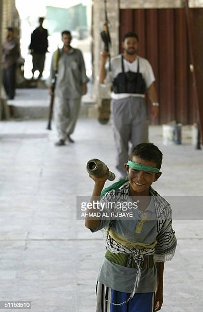 A young boy carries a rocketpropelled grenade as militiamen loyal to radical Iraqi Shiite Muslim cleric Moqtada Sadr clash with US and Iraqi forces...