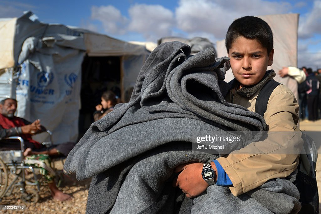 A young boy carries blankets as Syrian refugees go about their daily business in the Za'atari refugee camp on January 29, 2013 in Mafraq, Jordan. Record numbers of refugees are fleeing the violence and bombings in Syria to cross the borders to safety in northern Jordan and overwhelming the Za'atari camp. The Jordanian government are appealing for help with the influx of refugees as they struggle to cope with the sheer numbers arriving in the country.