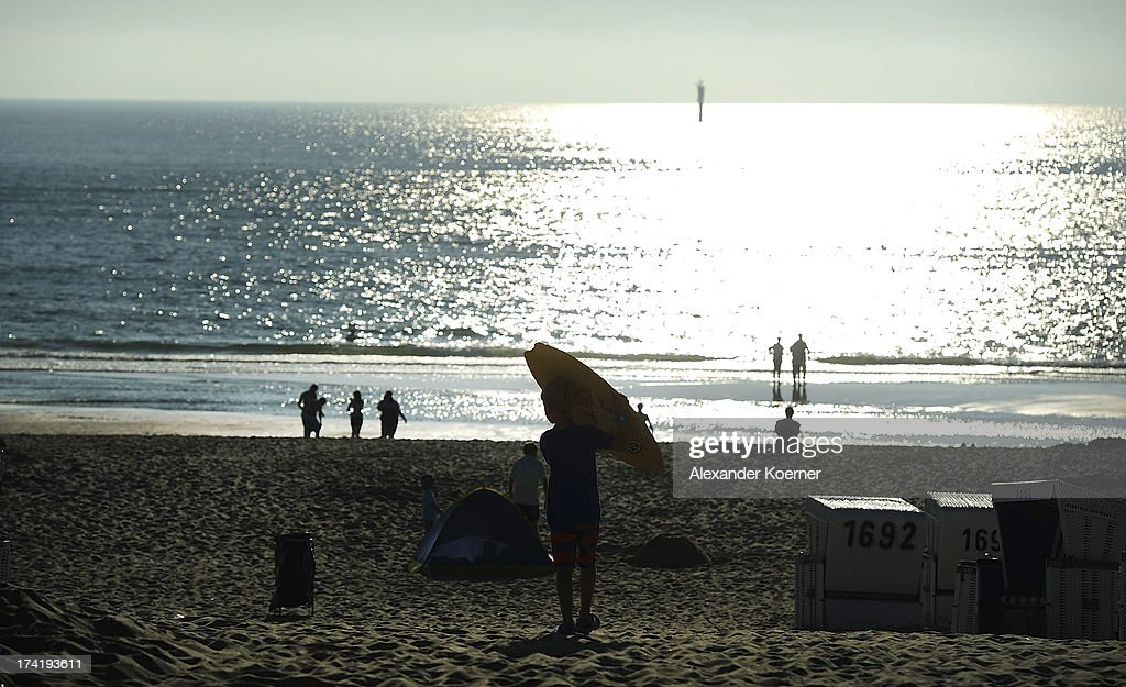 A young boy carries his surfboard towards shoreline of Brandenburger Beach on July 21, 2013 in Westerland, Germany. The weather forecast for the next three days predicts sunny weather with heights of 30 Celsius for the north of Germany.