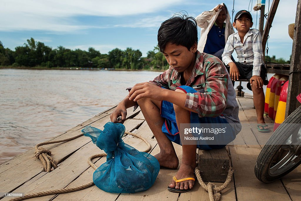 A young boy carries live chickens in a bag while crossing the Mekong by ferry south of Phnom Penh August 26, 2013 in Krong Preak village, Kandal Province, Cambodia. Cambodia has seen the worst out break of Avian influenza H5N1 since the disease was first identified, so far this year 17 cases have been report, 10 of which have been fatal.