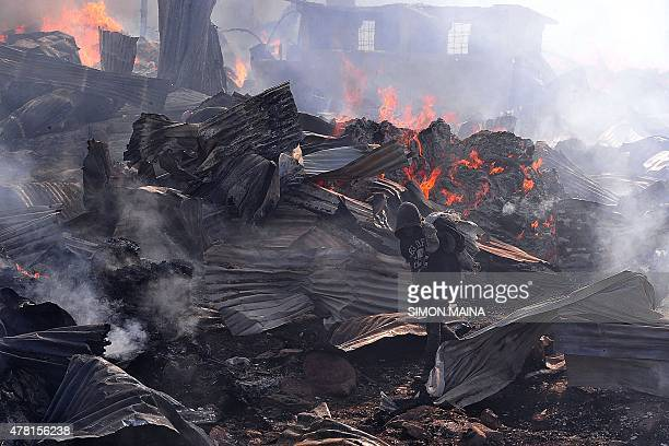 A young boy carrying metal to sell walks past as a fire burns through part of Gikomba market East Africa's largest second hand clothing market in...
