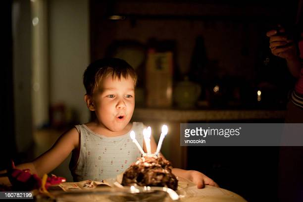 Young boy celebrating his fourth birthday with a cake