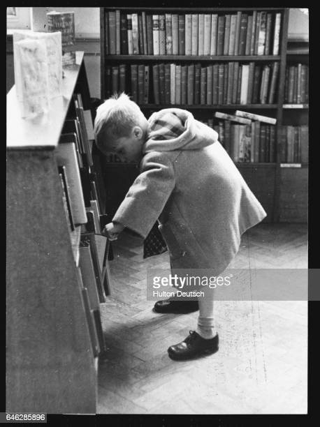 A young boy choosing a book to read at the Children's Library