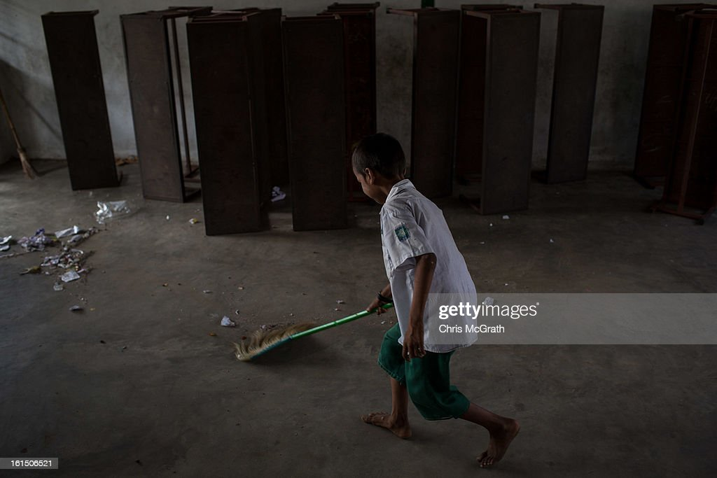 A young boy cleans up his class room after school at the Ahlal Taik Monastery School in Dala Township on February 11, 2013 in Yangon, Burma. The school provides basic education for orphans and children from poor areas. As the country goes through sweeping political and economic reforms, many are hopeful that after decades of neglect the healthcare system will also benefit from the changes. Although health budgets have increased the state health system is still underfunded and struggles to provide basic healthcare as well as essential medicines for treating HIV, Malaria and TB. With sanctions being lifted it is hopeful that again the flow of medical equipment, medicines and the presence of NGO's will increase.