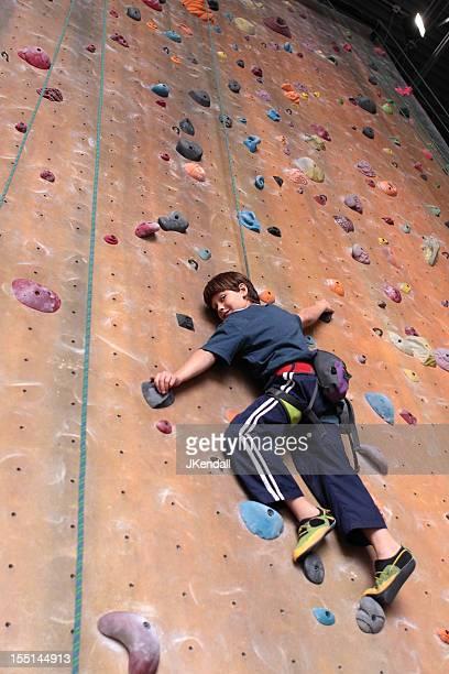 Young boy climbing a wall in a rock climbing gym