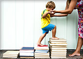 Young boy climbing steps made of books