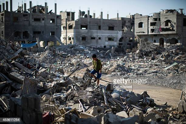 A young boy climbs through the rubble of a destroyed building on August 14 2014 in Beit Hanoun Gaza A new fiveday ceasefire between Palestinian...