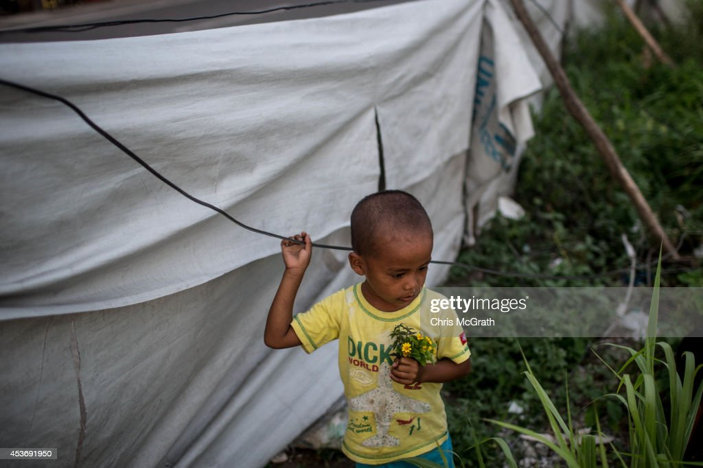 A young boy collects flowers at the San Jose evacuation complex on August 16, 2014 in Tacloban, Leyte, Philippines. Many families are still housed in temporary tent housing in the San Jose district. The families have been told that they will be rehoused before the visit of Pope Francis. Residents of Tacloban city and the surrounding areas continue to focus on rebuilding their lives nine months after Typhoon Haiyan struck the coast on November 8, 2013, leaving more than 6000 dead and many more homeless. With many businesses and government operations back up and running and with the recent start of the years typhoon season, permanent housing continues to be the main focus with many families still living in temporary accommodation. As well as continuing recovery efforts Leyte is preparing for the arrival of Pope Francis, who will visit the region from January 15- 19.