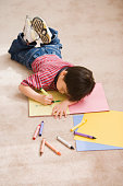 Young boy coloring on the floor