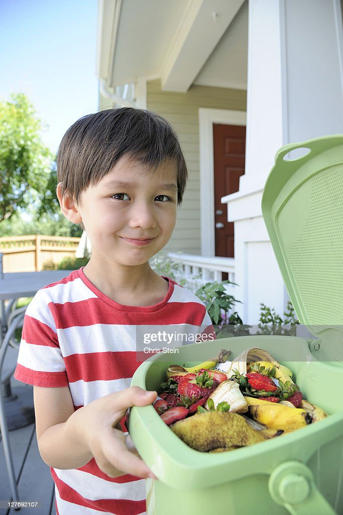 Young boy composting food scraps : Stock Photo