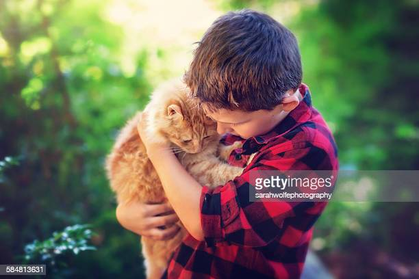 Young boy cradeling an orange cat outside