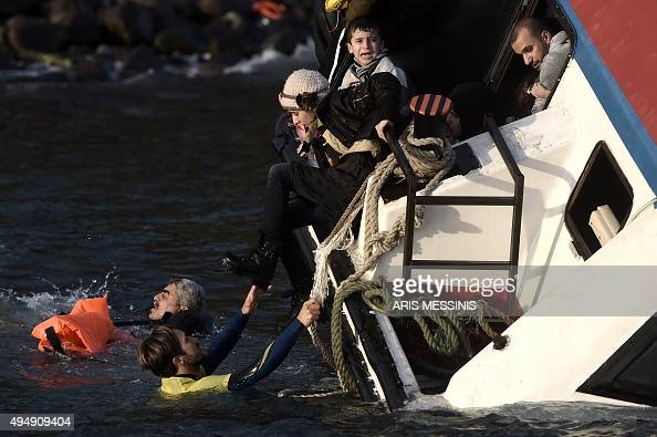 A young boy cries out for help with other refugees and migrants as their boat sinks off the Greek island of Lesbos island while crossing the Aegean...