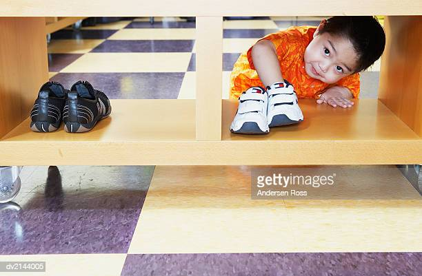 Young Boy Crouches on the Floor, Picking up a Trainer From a Shoe Rack