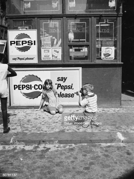 A young boy crouches with an instant camera photographing a young girl in front of a sign advertising Pepsi Cola 1970s