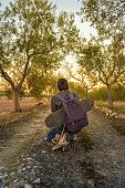 Young boy crouching and traveling for a rural path with a skateboard and a sneakers hanging of his backpack. Guy resting and looking the sunset.
