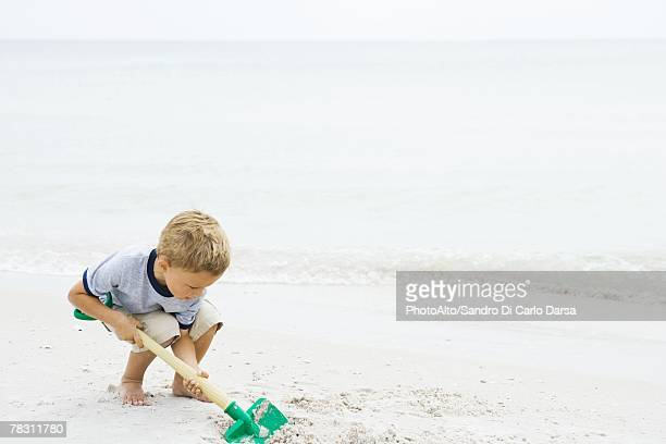 Young boy crouching at the beach, digging in sand with shovel