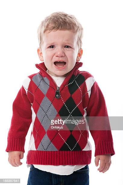 Jeune garçon pleurant isolé sur fond blanc