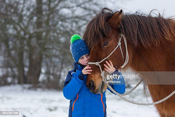 young boy cuddeling horse in winter