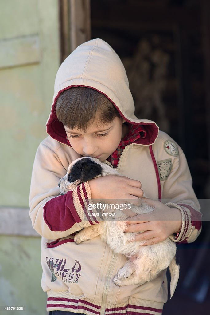 Young boy cuddle little street puppy : Stock Photo