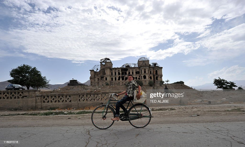 A young boy cycles past the ruins of Darulaman palace, the former residence of Afghan King Amanullah who reigned from 1920 to 1929, in Kabul on June 12, 2011. From a position of lonely authority, President Barack Obama faces wrenching political and even moral dilemmas as he plots a troop drawdown in Afghanistan due to begin next month.