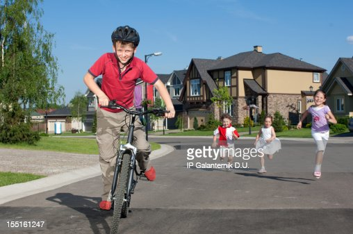 Young boy cycling by suburban street and children running behind
