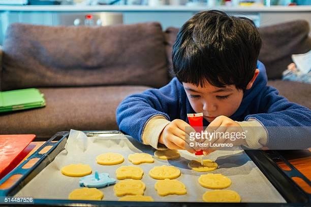 Young boy decorating biscuits
