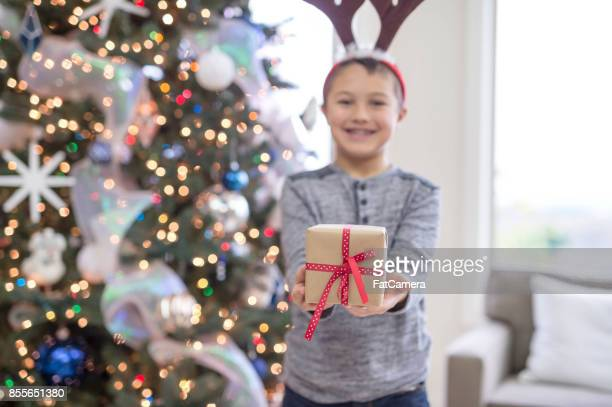 A young boy delightedly holds open a wrapped present