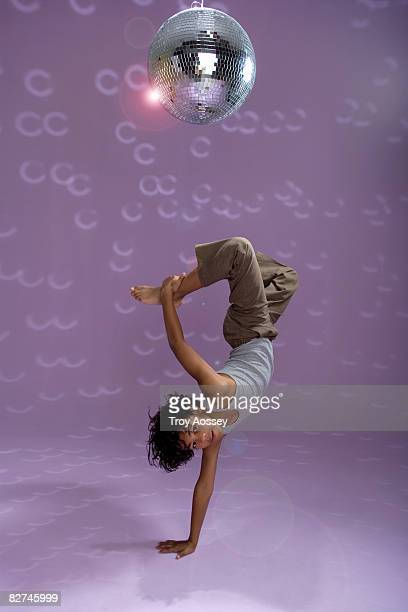 young boy doing a dance move under disco ball