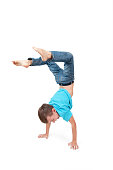 Young boy doing handstand with a white background