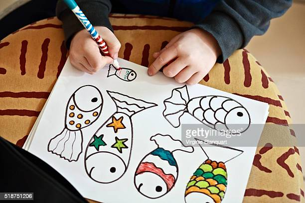 Young boy draws and colors fishes for April fool's day. 31st March 2016
