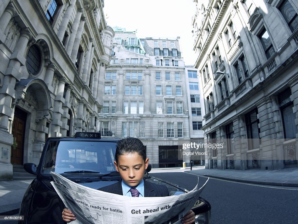 Young Boy Dressed as a Businessman Stands in a City Road Reading a Newspaper