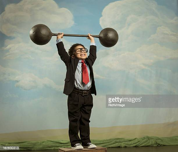 Young Boy Dressed as Businessman Lifting Barbell