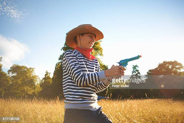 Young boy dressed as cowboy, holding toy gun