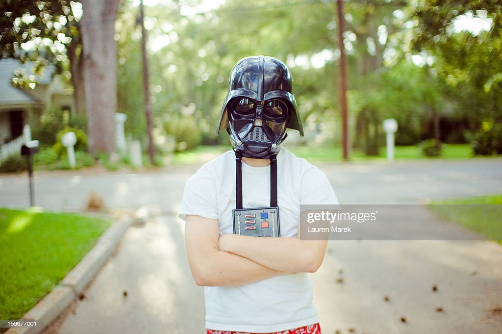CONTENT] A young boy dressed as Darth Vader from Star Wars standing outside his house.