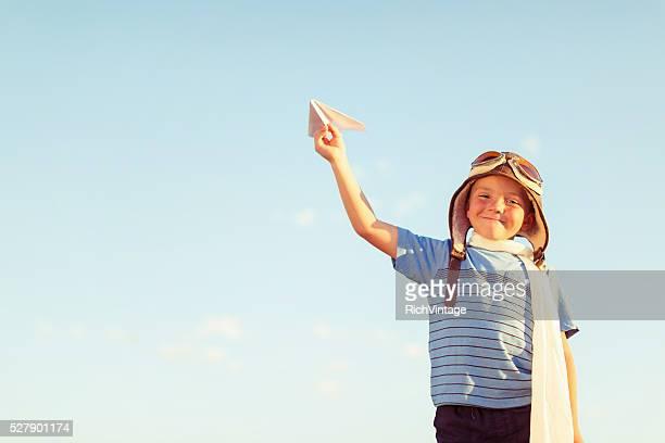 Giovane ragazzo vestito come pilota di volare Aeroplano di carta