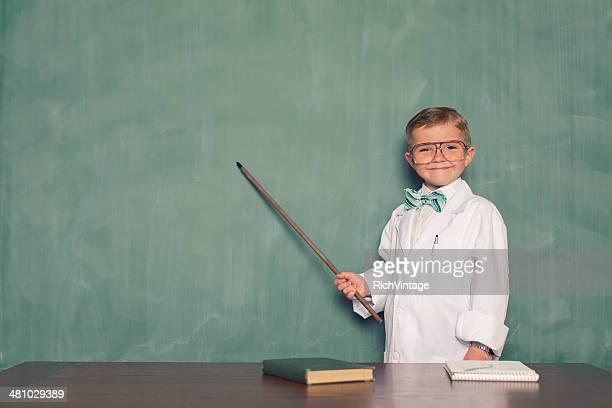 Rapaz jovem vestida como cientista pontos para Chalkboard