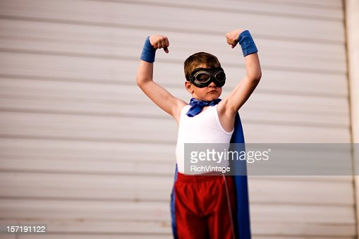 Young Boy Dressed as Supehero Flexes Biceps