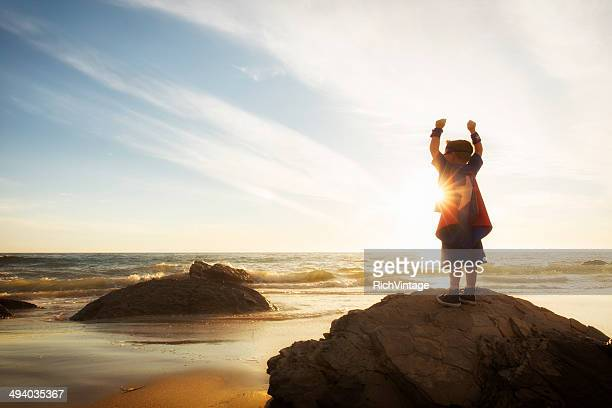 Young Boy Dressed as Superhero at Beach During Sunset