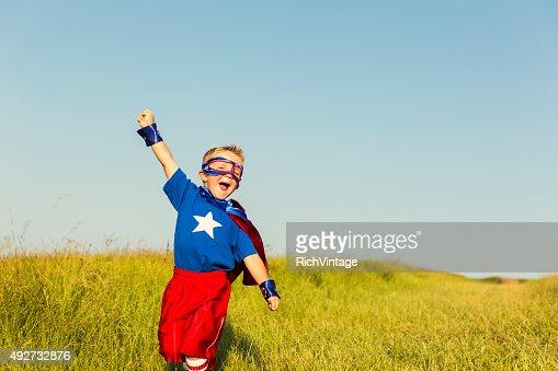 Young Boy dressed as Superhero Raises Arm