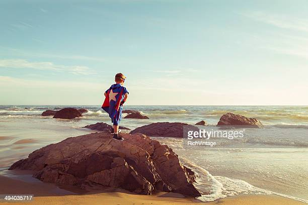 Young Boy Dressed as Superhero stands on California Beach