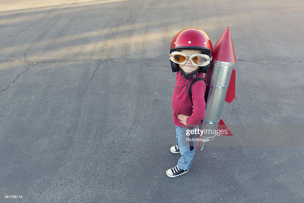 Young boy dressed in a red rocket suit on blacktop : Stock Photo