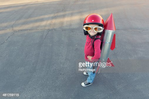 Young boy dressed in a red rocket suit on blacktop