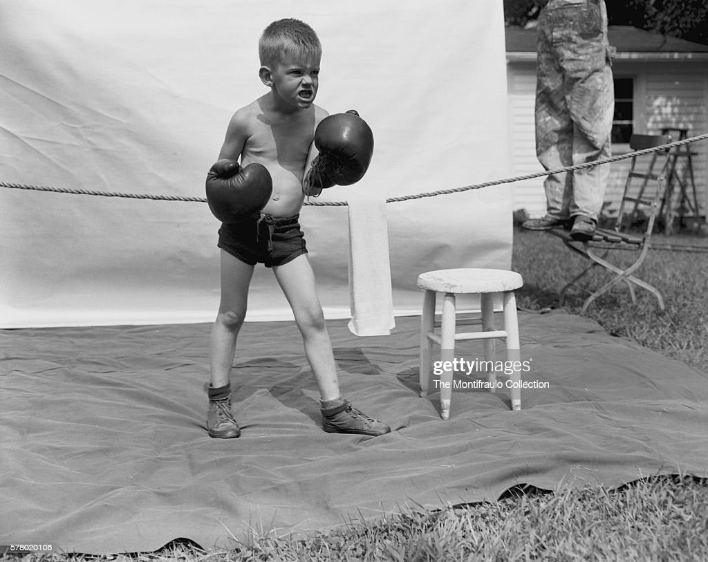 Young boy dressed in boxing trunks and wearing an oversized pair of boxing gloves growling in a posed fighting stance standing on a sheet inside a...
