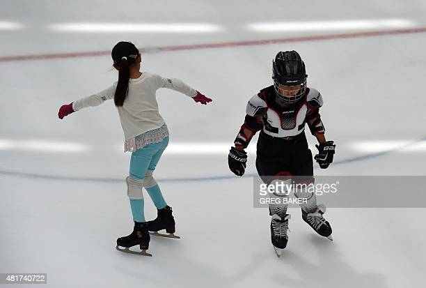 A young boy dressed in ice hockey uniform passes a girl practicing freestyle skating at an ice rink in Beijing on July 24 2015 Beijing is bidding to...
