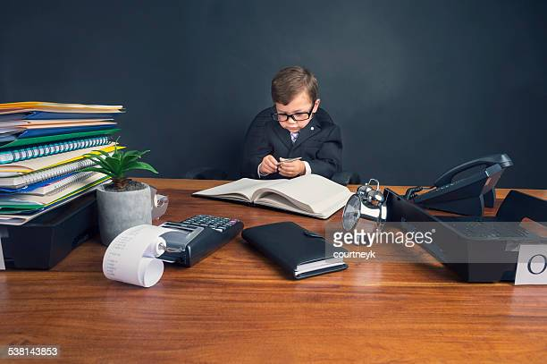 Young boy dressed in suit working at desk.