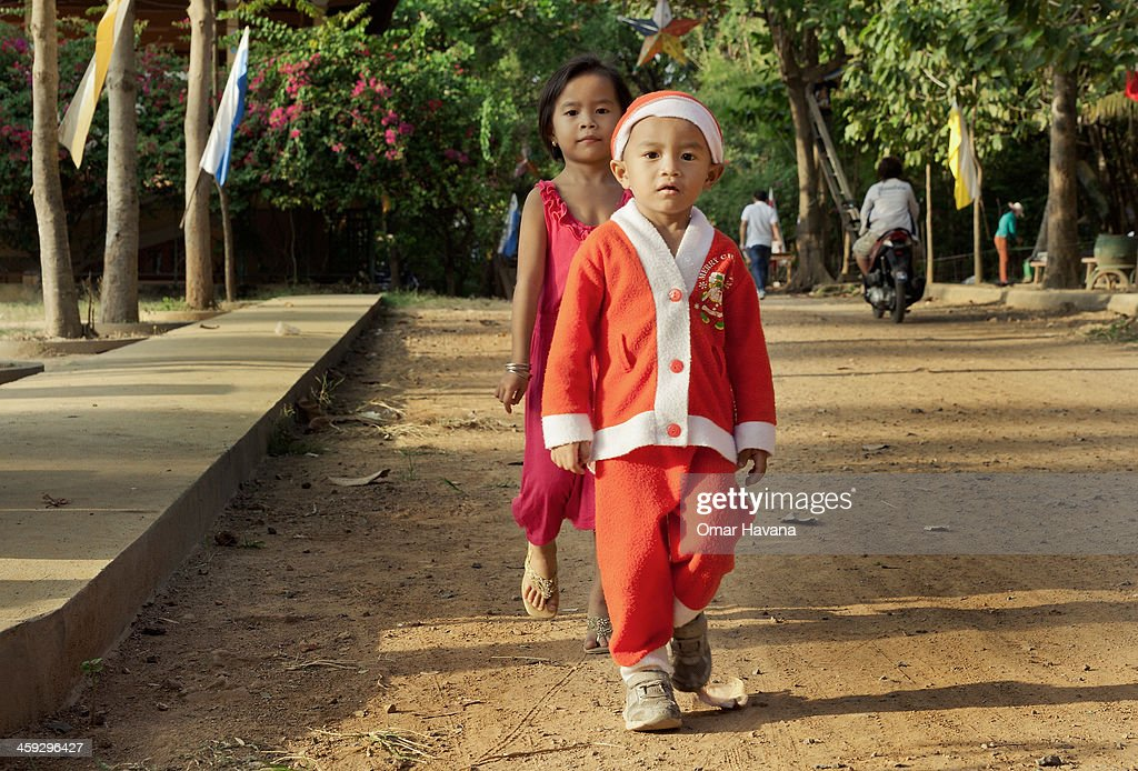 A young boy dresses as Santa Claus on Christmas Eve on December 24, 2013 in Battambang, Cambodia. The parish at Battambang dates back to 1790 when the Catholic community first arrived. Now they serve around 1000 Catholics and 600 families.