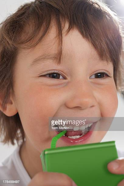 Young boy drinking juice box indoors